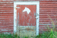 A Vintage Red Exterior Wall Of A Barn. There's A Small Old Door With White Trim In The Center. The Worn Wood Door And The Latch Has A Horse Head Painted In The Center. Green Grass Is In The Foreground