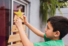Boy Painting Star Of Wooden Christmas Tree