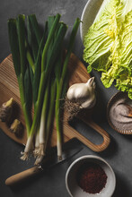 Ingredients To Make Kimchi, Including Napa Cabbage, Green Onions, And Gochugaru, Shot In Moody Lighting