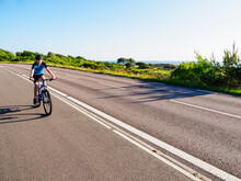Boy Cycling Along Country Road