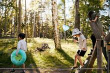 Children Crossing Wooden Fence
