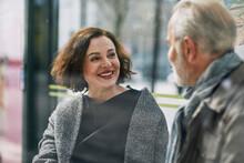 Smiling Woman Talking To Man At Bus Stop