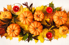 Multicolored Maple Leaves, Pumpkins And Candles On White Tablecloth Background. Autumn Composition In Flat Lay Style. Autumn, Fall, Halloween, Thanksgiving Day Concept.