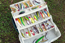 Set Of Colorful Fishing Lures In Open Fishermans Tackle Box In Summer
