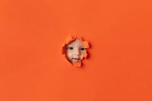Young Baby Peeking Through Orange Paper