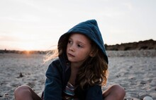Portrait Of A Young Girl Sat At The Beach At Sunset