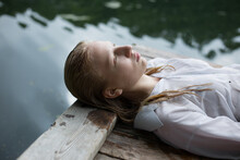 Blonde Teenage Girl  In White Shirt With Wet Hair Is Lying By The Lake