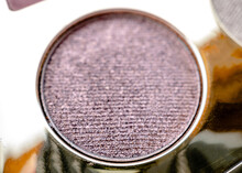 A Close-up Of Pearlescent Shimmery Purple Eyeshadow For Creating Eye Makeup.