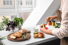 Woman Spreading Toast With Dip At Table In Kitchen