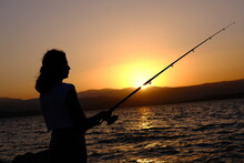 Silhouette Of Woman Fishing At Sunset.