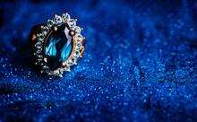 Closeup Of Luxury Wedding Ring In Dark Blue Glitter Background. Bridal Golden Jewelry Gift With Precious Gemstone.