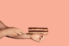 A Cake On A Background With A Woman's Hand Is A Modern Dish Of A Minimalistic Concept That Copies The Space. The Concept Of A Cafe Or Bakery With Desserts. Your Choice, A Good Offer. Profitable.