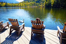 A Girl Is Resting On A Wooden Sun Lounger On The Shore Of An Emerald Lake On A Warm Autumn Day. A White Swan Is Swimming Nearby. Travel And Outdoor Recreation Concepts.