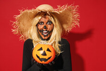 Young Woman With Halloween Makeup Mask Wears Straw Hat Black Scarecrow Costume Hold Pumpkin Jack-o-lantern Say Boo Isolated On Plain Red Background Studio Portrait. Celebration Holiday Party Concept