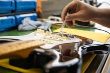 Faceless Man Setting Up Guitar Bridge