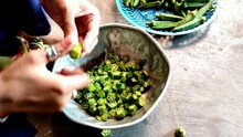 A Closeup Of A Person Cutting Raw Okras In Slices Into A Bowl Shot In 4K