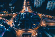 Night Lights From Car Headlights On Roundabout In Night City. Traces Of Headlights On The Road At Night, Long Exposure. Drone Aerial Shot.