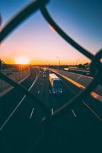Vertical Shot Of An Expressway Against A Beautiful Sunset Sky As Seen Through A Caged Footbridge