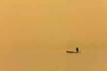 Man Fishing From Boat At Sunset