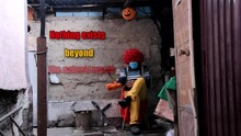 """A Clown Decorates His Place With A Halloween Pumpkin Lantern, Lights A Fire And Warms His Hands. The Screen Says: """"Nothing Exists Beyond The Natural World. So Don't Be Afraid And Celebrate Halloween"""""""