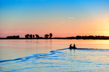 Two Men Navigate The Lagoon With A Small Boat At Sunset