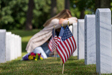 A Grieving Woman Shares Her Emotions With Her Fallen Veteran Family Member At A MIlitary Cemetery