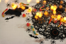 Top View Image Of Halloween Holoday. Witcher Broom, Treats, Spiders And Bats Over White Wooden Table