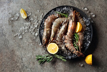 Fresh Tiger Prawns In A Black Plate With Lemon, Rosemary And Crushed Ice.