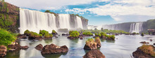 Iguazu Waterfalls In Argentina, View From Devil's Mouth. Panoramic View Of Many Majestic Powerful Water Cascades With Mist And Clouds. Panoramic Image Of Iguazu Valley With Stones In Water.