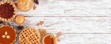 Selection Of Homemade Autumn Pies. Pumpkin, Apple And Pecan. Above View Corner Border On A White Wood Background With Copy Space.