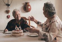 Senior Woman With Female Guest Celebrating Birthday