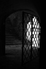 The Interior Of An Abandoned Gothic Castle With An Iron Lattice Door. Mystery Halloween Scary Place For Ghosts.