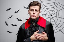 Vampire Halloween Concept - Portrait Of Handsome Caucasian In Vampire Halloween Costume Holding Hand On Heart.