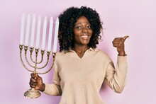 Young African American Woman Holding Menorah Hanukkah Jewish Candle Pointing Thumb Up To The Side Smiling Happy With Open Mouth
