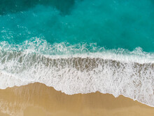 Aerial Drone View Of Waves Crushing On Tropical Beach With Sand. Waves Breaking On The Shore At Sunset. Transparent Sea Water.