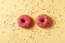 Two Pink Donuts Close Up With Sprinkles On Yellow Background,