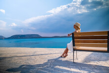 Woman In Sun Straw Hat Sitting On A Wooden Bench At Ermioni Marina, Greece