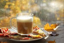 Cup Of Frothy Coffee And Slices Of Pizza On A Plate Against The Background Of A Window After The Rain. Food And Drink In Autumn Style