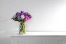 Bouquet Of Colorful Asters Are On A White Dresser