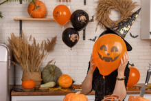 An Unrecognizable Woman Holding A Scary Halloween Face In Front Of Her Face, A Bright Orange Balloon. A Woman In A Carnival Pointy Hat Hides Her Face Behind A Pumpkin Lantern.
