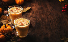 Pumpkin Butter Latte Or Coffee, Keto Drink On Wooden Table With Fallen Leaves, Small Pumpkins, Pine Cones And Nuts. Autumn And Winter Hot Drink And Beverage