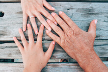 Top View Of Family Members' Hands On A Wooden Table, Three Generations Of Women