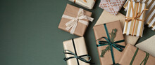 Christmas Background With Gift Boxes Over Green Backdrop. Xmas Celebration, Preparation For Winter Holidays, Secret Santa, Advent Calendar Concept. Festive Banner, Website Header, Top View, Flat Lay
