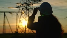 Civil Engineer, Woman Specializing In Electricity Supply Works Outdoors. Environmentally Friendly Electricity. Modern Technologies. Power Engineer In Safety Helmet Checks Power Line, Digital Tablet