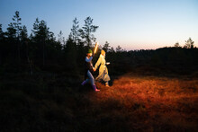 Two Young Women Get Lost In Countryside After Sunset Walk Holding Hands Highlighting Trail Or Pathway With Led Lamp. Female Friends Returning From Forest After Hiking In Autumn Nature At Night In Dusk