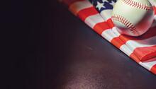 American Traditional Sports Game. Baseball. Concept. Baseball Ball And Bats On A Table With American Flag.
