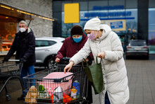 Senior Woman And Social Worker With Medical Mask Due Pandemic Coronavirus Disease. Daughter Or Granddaughter Help Grandmother With Shopping In Supermarket, Push Cart Trolley With Foods, Outdoors