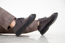 Brown Female Or Male Patent Leather Shoes On Legs Of Woman. Shooting For A Catalog Or An Online Store. A Pair Of Shoes