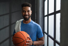 Happy Young African American Basketball Player Standing Indoors At Gym, Looking At Camera.