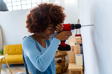 Cheerful Redhead Woman Leaning On Power Drill At Home